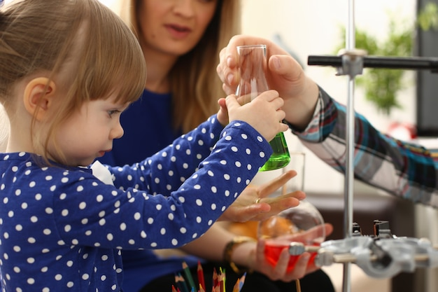 Frau und kleines mädchen spielen mit bunten flüssigkeiten