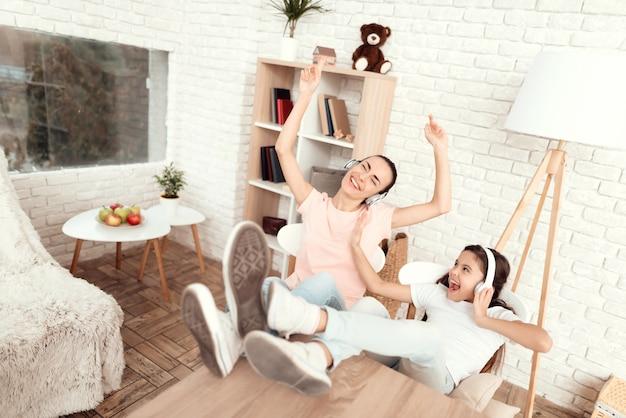 Frau und mädchen hören musik mit kopfhörern und entspannen sich.