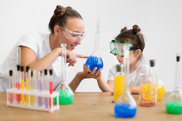 Frau und mädchen mit schutzbrille im labor