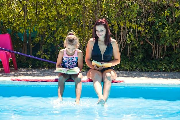 Frau und mädchen sitzen am pool lesen