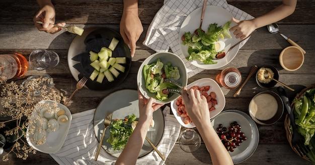 Frau und mann abendessen mit bio-salat, lebensmittel gesundes bio-gemüse-konzept mit draufsicht