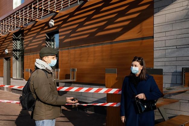 Frau und mann auf der straße tragen maske