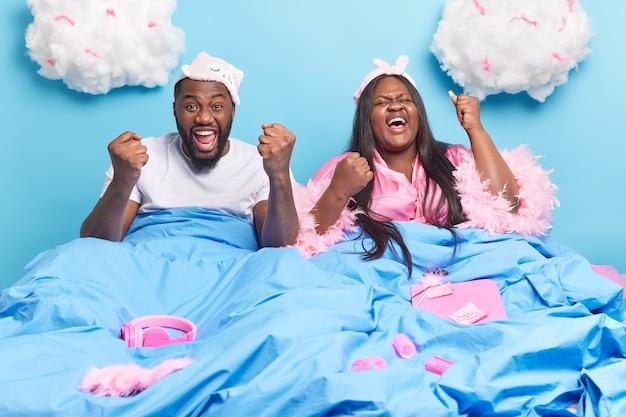 Frau und mann ballen die fäuste, freuen sich über das wochenende und die freizeit posieren im bett unter einer weichen decke, die in häuslicher kleidung isoliert auf blau gekleidet ist