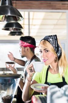 Frau und mann barista im asiatischen café, das kaffee vorbereitet