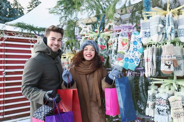 Frau und mann beim einkaufen auf dem weihnachtsmarkt