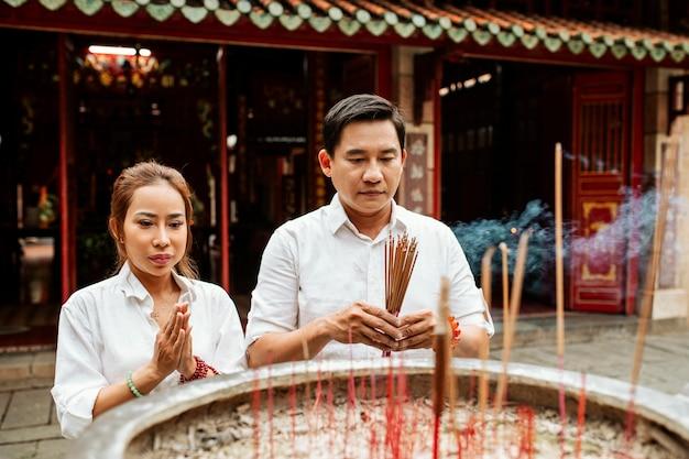 Frau und mann beten am tempel mit brennendem weihrauch