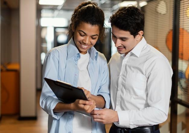 Frau und mann betrachten zwischenablage zusammen am arbeitsplatz