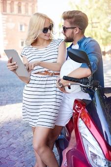 Frau und mann, die digitales tablett in der stadt verwenden