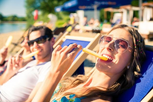 Frau und mann, die eiscreme auf strand essen