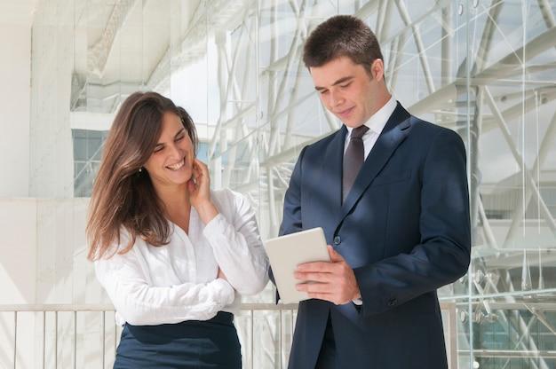 Frau und mann, die im korridor stehen, mann, der daten bezüglich der tablette zeigt