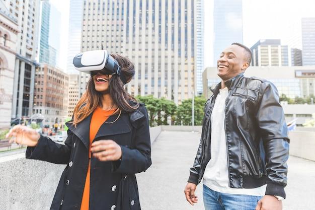 Frau und mann, die mit kopfhörer der virtuellen realität lächeln und spielen