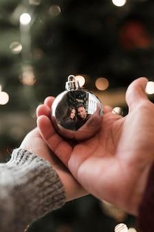 Frau und mann, die verzierungsball mit reflexion halten