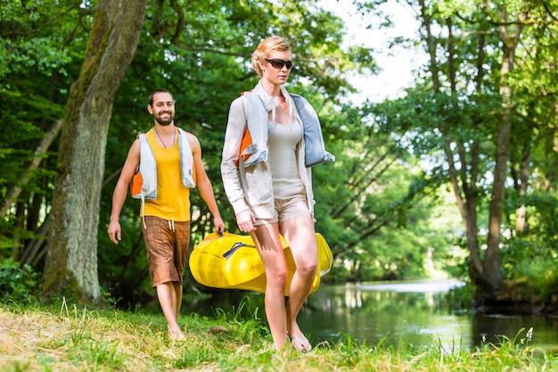 Frau und mann, die zusammen kajak zum waldfluß tragen