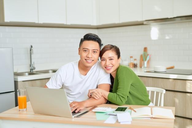 Frau und mann erledigen gemeinsam papierkram und zahlen online steuern auf dem notebook-pc