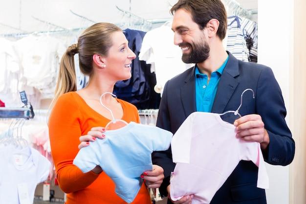 Frau und mann erwarten zwillinge, die babykleidung kaufen