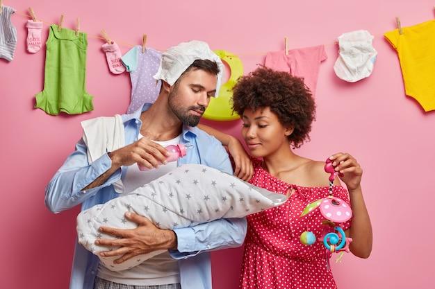Frau und mann gemischter rassen kümmern sich um das spiel mit kleinen babynahrungsmitteln, wobei das neugeborene kind gute eltern ist. vater füttert kleine tochter in decke gewickelt. mutter sieht schlafendes kind an. familienelternschaft