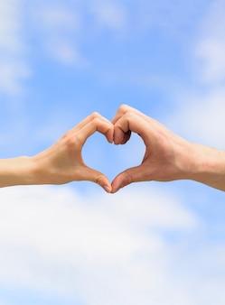 Frau und mann hände in form von herzen gegen den himmel. hände in form des liebesherzens. herz von den händen auf einem himmelshintergrund.