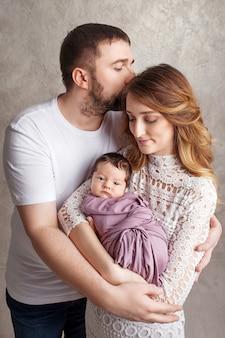 Frau und mann halten ein neugeborenes. mama, papa und baby. porträt der glücklichen familie mit neugeborenem an den händen