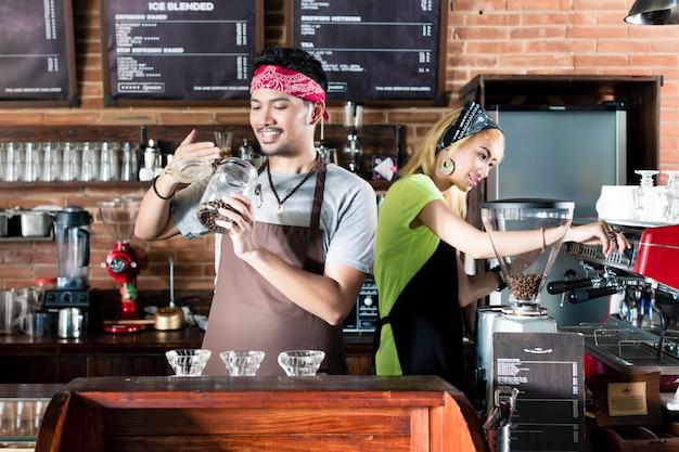 Frau und mann im asiatischen café, das kaffee vorbereitet