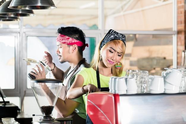 Frau und mann im asiatischen café, das kaffee zubereitet