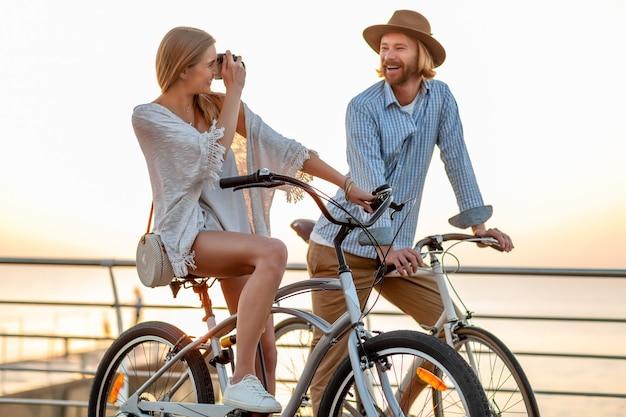 Frau und mann in der liebe, die auf fahrrädern am sonnenuntergangsmeer reist