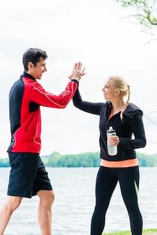 Frau und mann in der pause vom laufen geben sich gegenseitig eine hohe fünf