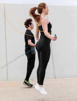 Frau und mann in der sportbekleidung, die draußen trainiert