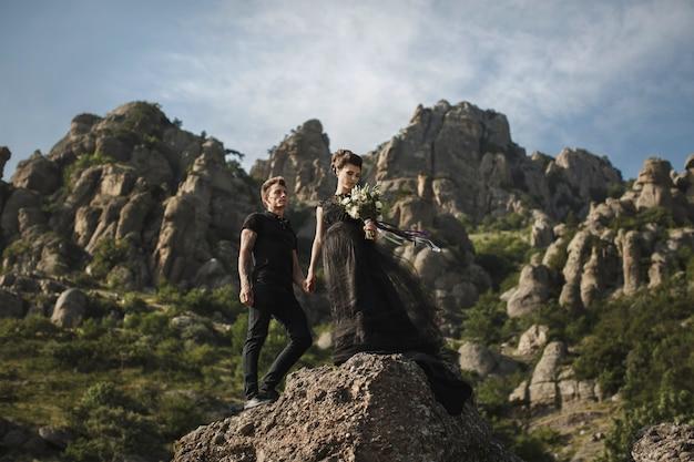 Frau und mann in schwarzer kleidung im freien. schwarzes hochzeitskleid.