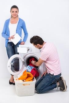 Frau und mann machen wäsche mit waschmaschine.