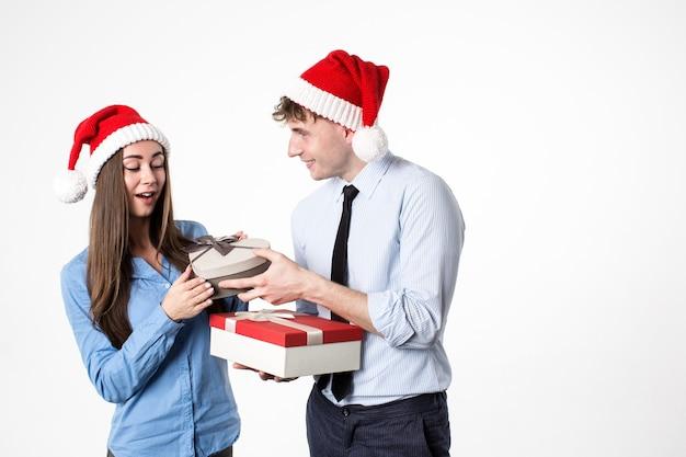 Frau und mann mit geschenk für neujahr und weihnachten in der weihnachtsmütze lokalisiert