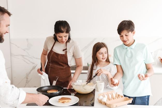 Frau und mann mit glücklichen kindern jungen und mädchen 8-10 zusammen kochen und pfannkuchen auf modernem herd in der küche braten