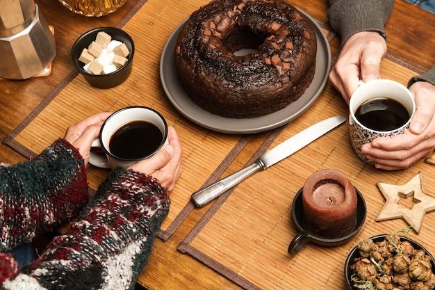 Frau und mann mit kaffeetassen und einem runden schokoladenkuchen auf einem holztisch
