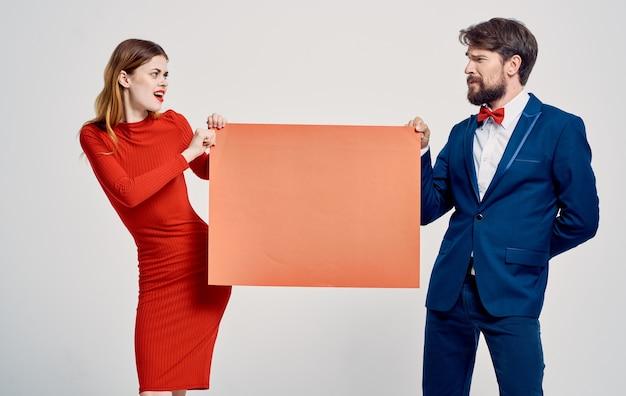 Frau und mann mit rotem blatt papier und modellwerbung auf grauem hintergrund