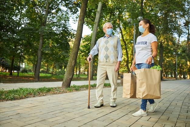 Frau und mann mit schutzmasken auf der straße