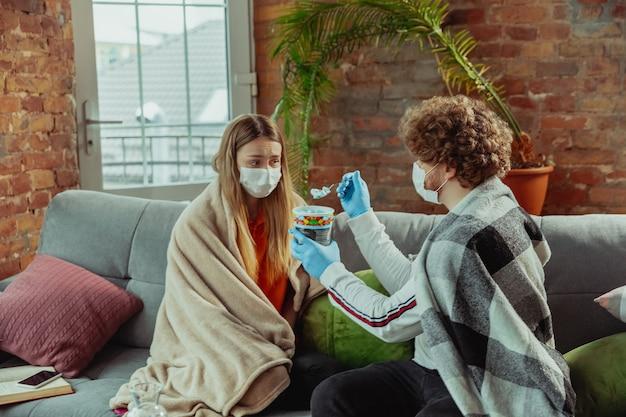 Frau und mann, paar in schutzmasken und handschuhen, die zu hause mit atemwegssymptomen des coronavirus wie fieber, kopfschmerzen, husten isoliert sind. gesundheitswesen, medizin, quarantäne, behandlungskonzept.