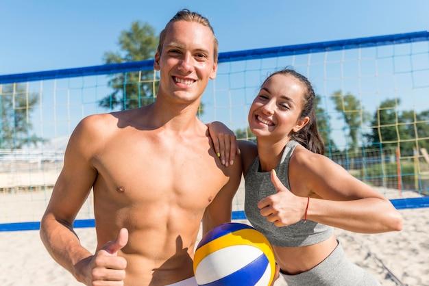 Frau und mann posieren mit daumen hoch, während sie beachvolleyball spielen