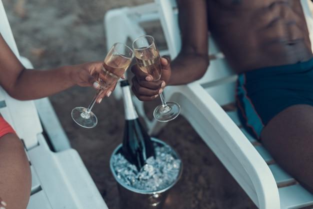 Frau und mann röstet gläser mit champagner am strand