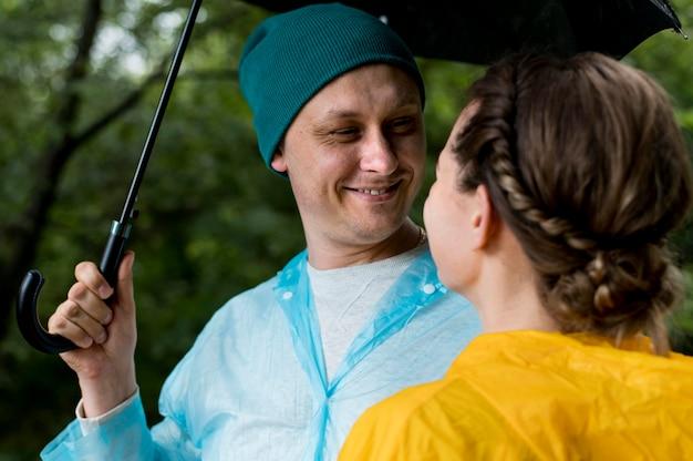 Frau und mann schauen sich unter ihrem regenschirm an
