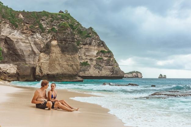 Frau und mann sitzen an einem diamantstrand auf der insel nusa penida