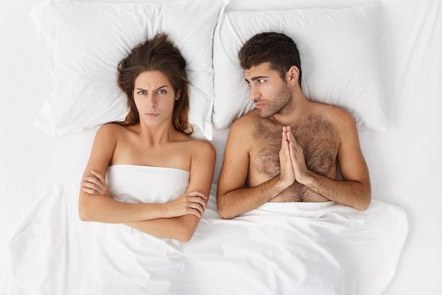 Frau und mann sitzen in der draufsicht des bettes