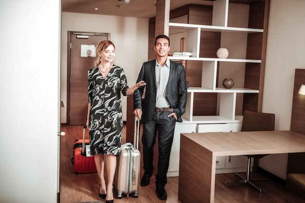 Frau und mann. stilvolle frau und ehemann, die beim betreten ihres hotelzimmers aufgeregt sind