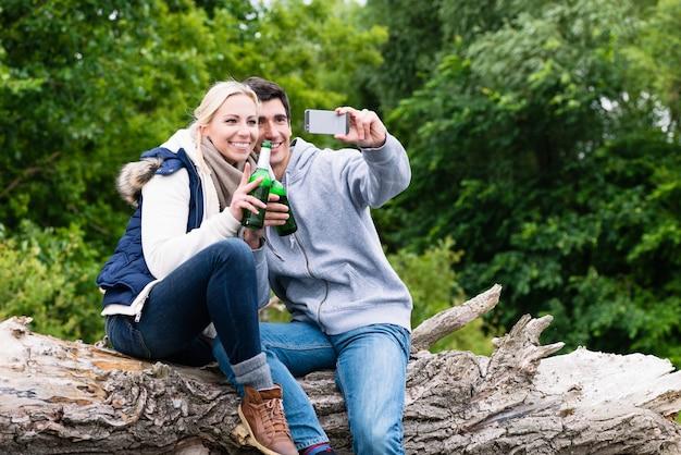 Frau und mann trinken bier, das selfie beim wandern im wald nimmt