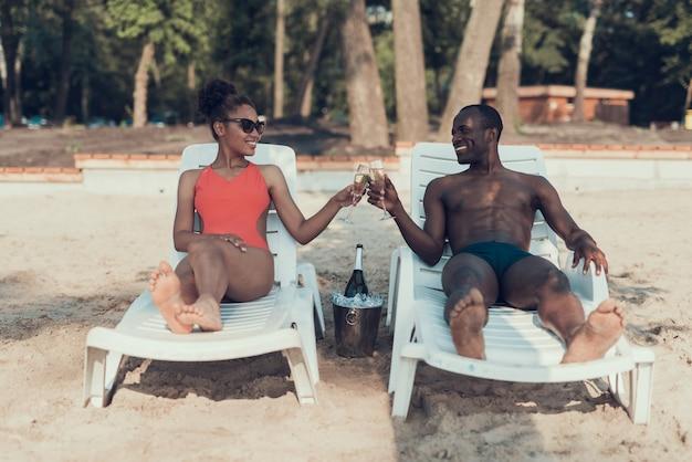 Frau und mann trinkt champagner auf sandy river beach