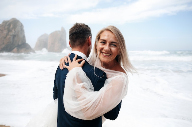 Frau und mann umarmen stehen am ozeanstrand