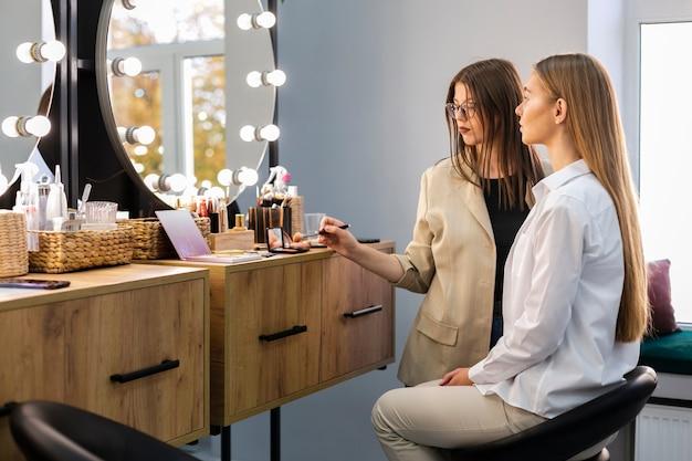 Frau und maskenbildner, die spiegel betrachten