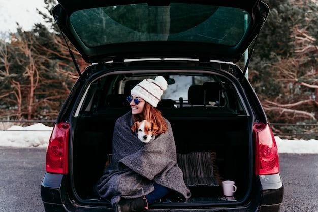 Frau und niedlicher jack russell hund genießen draußen am berg in das auto. reisekonzept. wintersaison