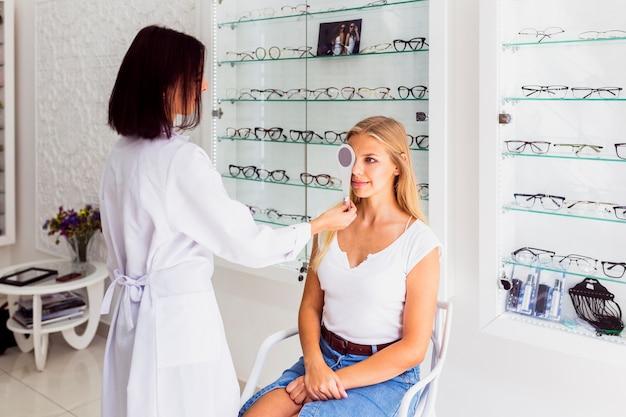 Frau und optiker während der augenuntersuchung