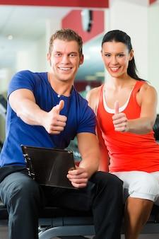 Frau und personal trainer im fitnessstudio mit hanteln