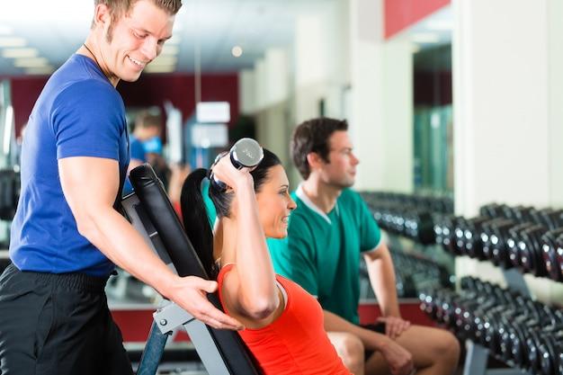 Frau und personal trainer im fitnessstudio, mit hanteln
