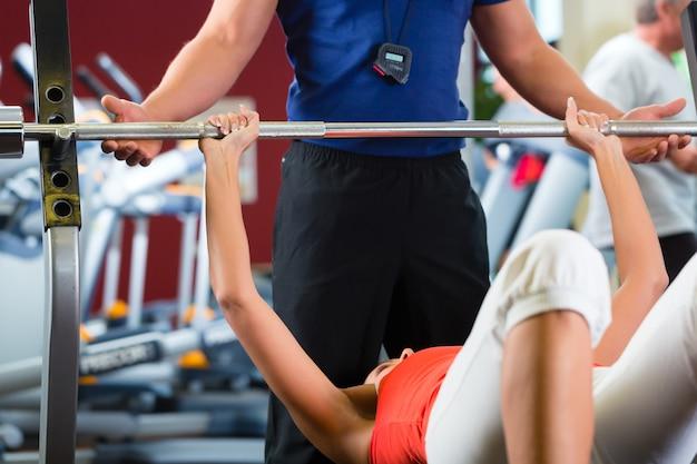 Frau und personal trainer im fitnessstudio